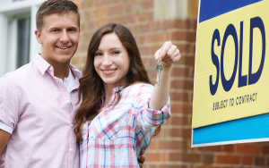 couple-with-keys-and-sold-sign